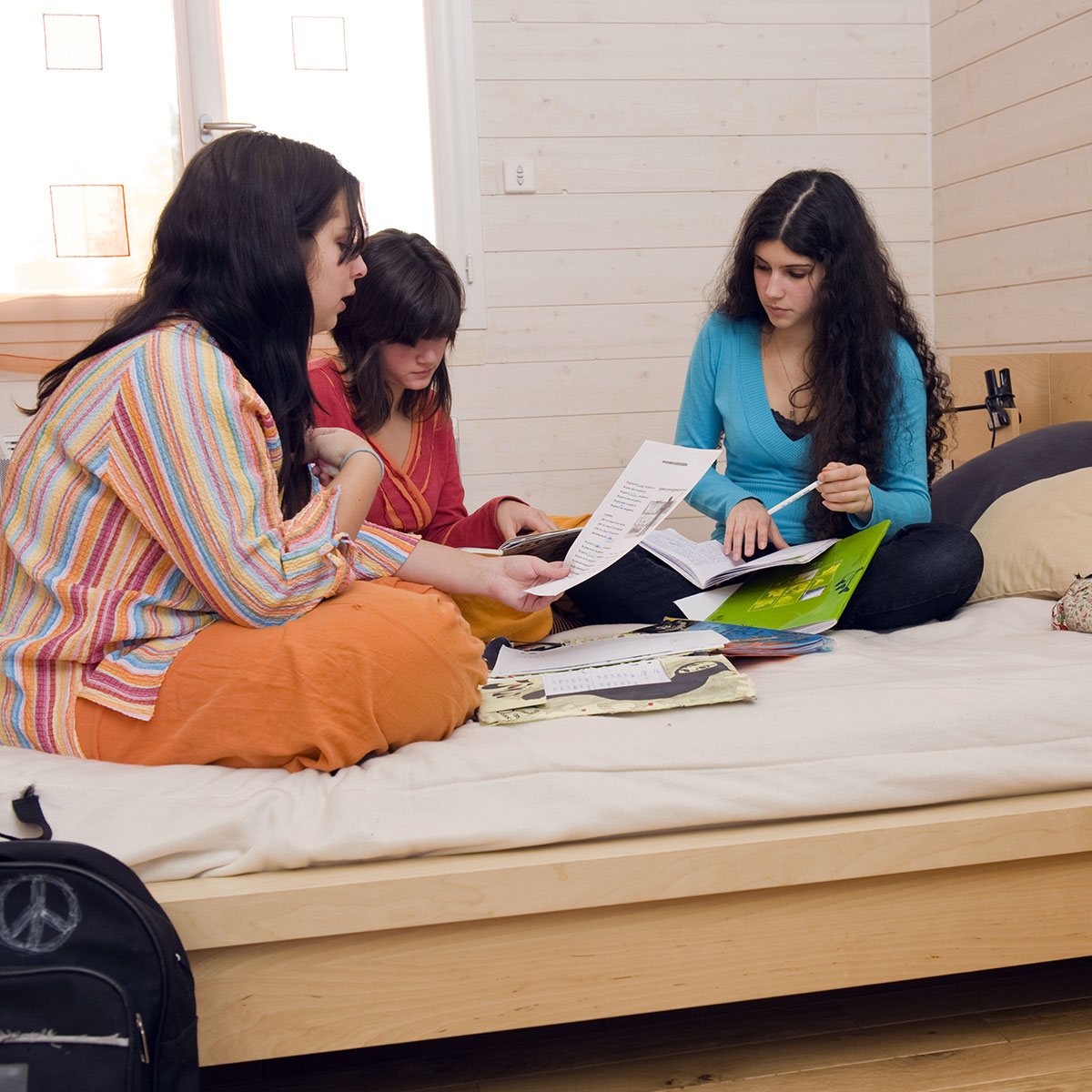 Image of three girls working together in their dorm room