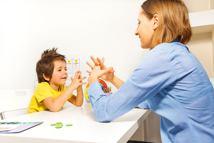 Image of autistic boy working with caregiver at home