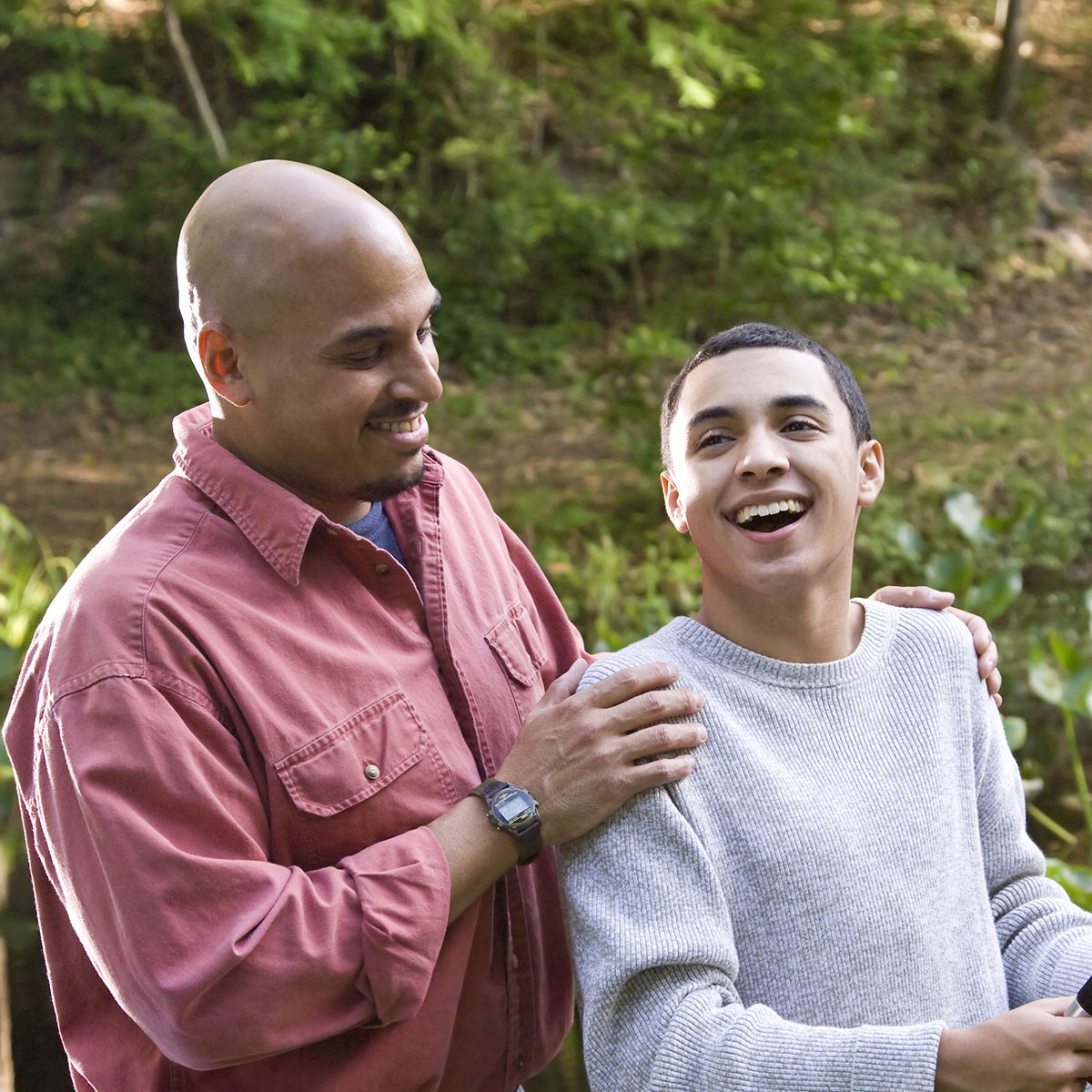 Image of happy Hispanic father with hands on the shoulder of his laughing son